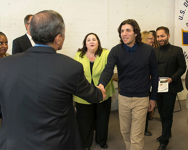 Rutgers student shaking hands with USDOT Deputy Secretary Mendez