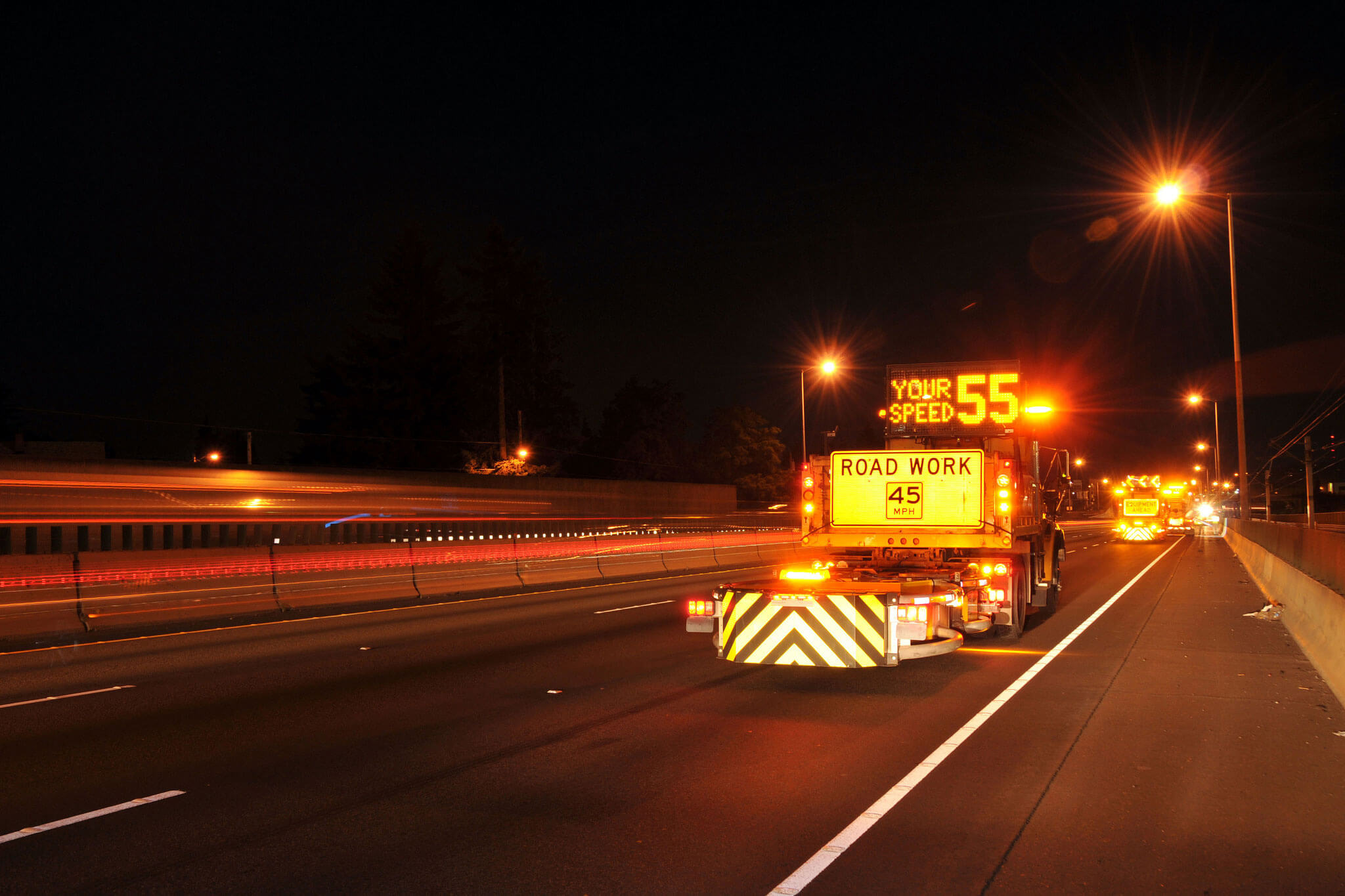 safety attenuator truck on highway road project at night