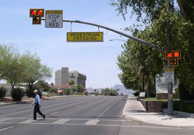 man crossing the street under a pedestrian crosswalk beacon and sign