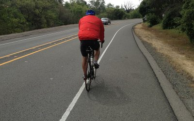 cyclist riding on a wide paved roadway shoulder