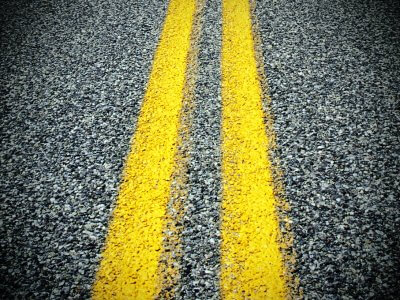 closeup of asphalt pavement and yellow lines