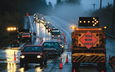 rainy road work zone with attenuator truck and lane closed arrow