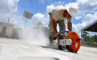 worker cutting concrete with a power saw in a cloud of dust