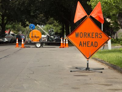 orange diamond 'workers ahead' warning sign posted before a road repair project