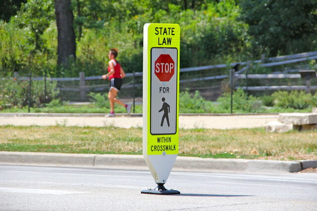 an in-street stop-for-pedestrians sign with runner in the background