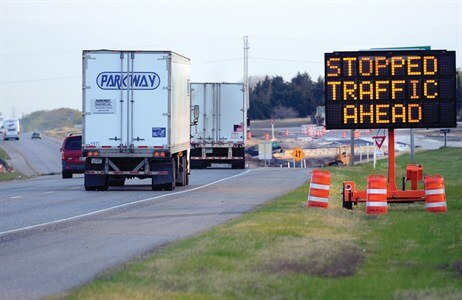 highway work zone sign with tractor trailer and other traffic