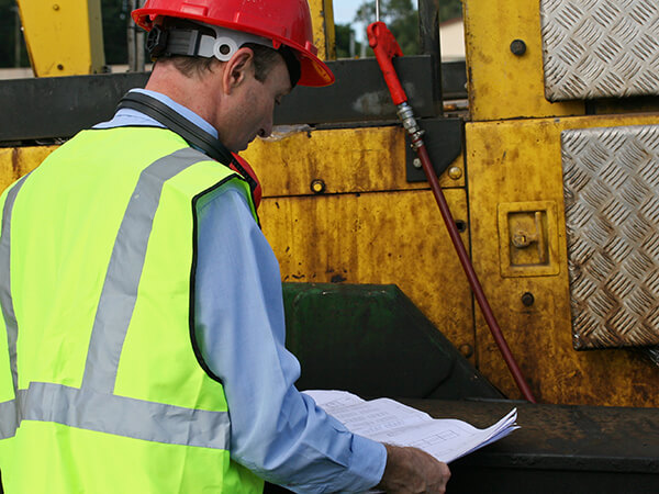 construction engineer looking a plans next to some heavy equipment