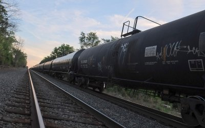 long freight train made up of tanker cars stretches to the horizon
