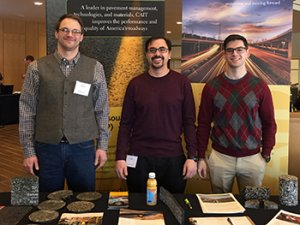 Three CAIT paving lab personnel at a table with literature and asphalt samples
